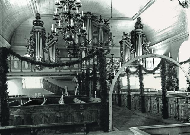 Die Kirche des Ortes zur Weihnachtszeit im Schmuck von Lichtbögen und Wacholder. Archiv der Hütte.